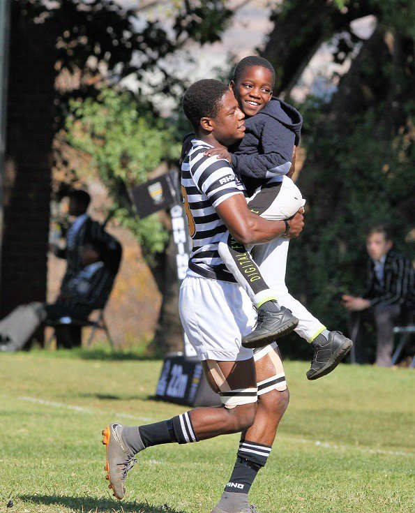 Muzi Manyike carries a boy from a local orphanage onto the field ahead of the second Jeppe v KES derby game.