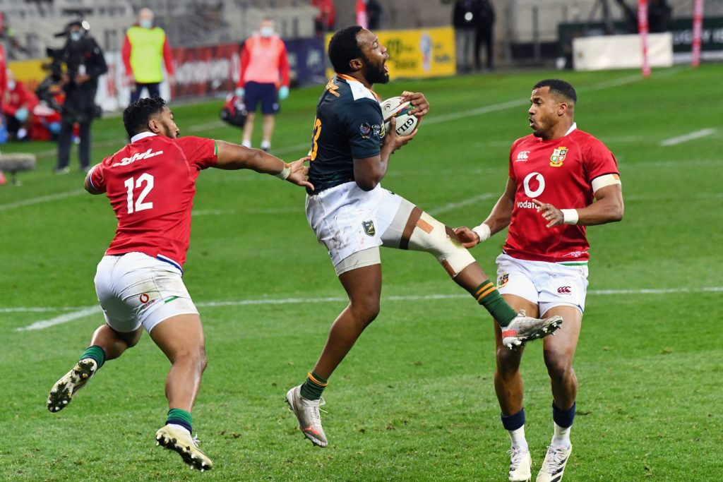 """South African captain Lukhanyo Am (C) grabs the ball in a line out from Bundee Aki (L) and Anthony Watson of British & Irish Lions during the Rugby union match between the South Africa """"A"""" and the British and Irish Lions at Cape Town Stadium on July 14, 2021 in Cape Town. (Photo by RODGER BOSCH / AFP)"""